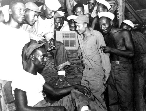 Men of 22nd Special Construction Battalion in the Admiralty Islands listen to radio acocunts of V-J Day