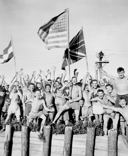 Liberated Allied POWs  cheer and wave their countries' flags at Yokohama
