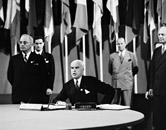 Harry Truman and Secretary of State Edward R. Stettinius, Jr., at the signing of the United Nations charter